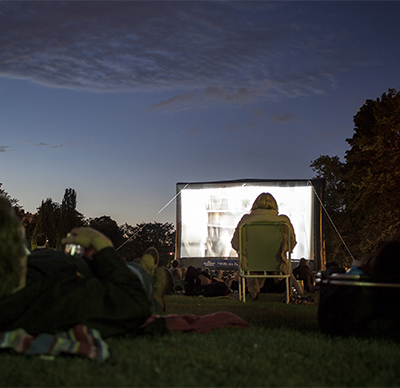 Spectators at Open-Air Cinema event at Reisinger park in the city center of Wiesbaden.